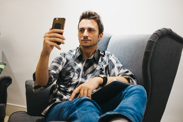 Smiling young man using smartphone near laptop on armchair