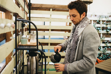 Young man with scarf filling cup from kettle