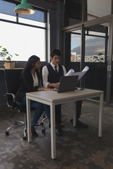 Executives discussing over blue print while using laptop