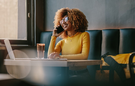 Businesswoman talking over mobile phone sitting at a restaurant