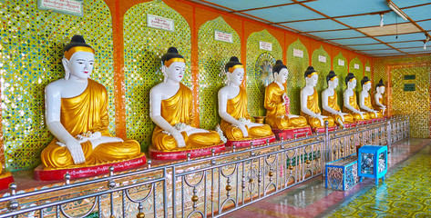SAGAING, MYANMAR - FEBRUARY 21, 2018: The line of Buddha Images in Image House of U Min Thonze Temple, the wall is decorated with fine mirror patterns, on February 21 in Sagaing