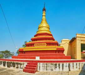 The beautiful relief pagoda of U Min Thonze Temple with red and gilt belts and old hti umbrella on the top, Sagaing, Myanmar.