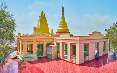SAGAING, MYANMAR - FEBRUARY 21, 2018: Panorama of the pagoda of U Min Thonze Caves site with covered pavilions and golden stupa, decorated with carved patterns, on February 21 in Sagaing