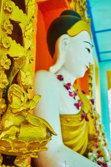 SAGAING, MYANMAR - FEBRUARY 21, 2018: The close-up of the Buddha image with small sculpture of praying golden Nat (Spirit-deity) on the foreground, U Min Thonze Temple, on February 21 in Sagaing