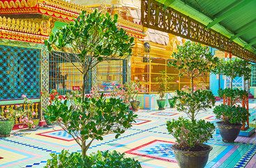 SAGAING, MYANMAR - FEBRUARY 21, 2018: The courtyard of Soon Oo Ponya Shin Paya (Summit Pagoda) is decorated with green plants and bright flowers in pots, on February 21 in Sagaing