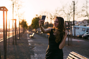 Young woman taking selfie on smartphone on alley