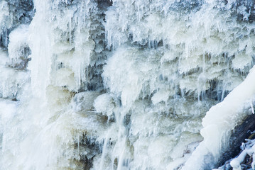 Frozen water. A view of the snow-covered Keila waterfall on a sunny winter day, close-up. Estonia