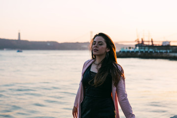 Cheerful young woman in casual wear near water on promenade