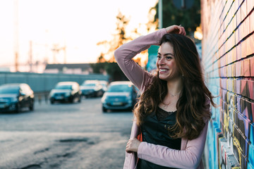 Young smiling woman in casual wear near wall