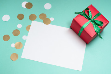 Decorated gift box, confetti and blank white sheet of paper.