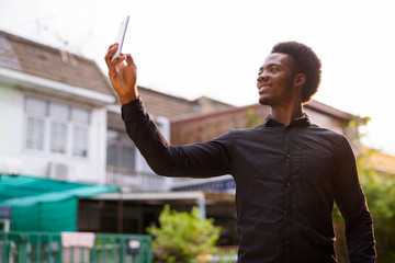 Young handsome African man using mobile phone outdoors