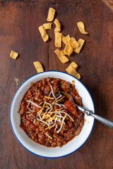 bowl of chili with beans and tomatoes topped with shredded cheese with side of corn chips flat lay