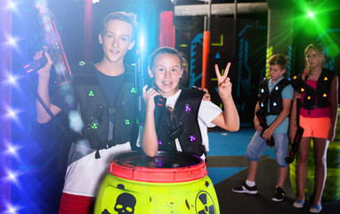 Girl and boy with laser pistols in laser tag labyrinth