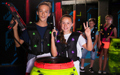Girl and boy with laser guns on lasertag arena