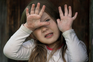 A young little girl with her hands closed, puts her palms in front of her, so that she can close herself from danger, fear, stress, trouble, aggression, violence
