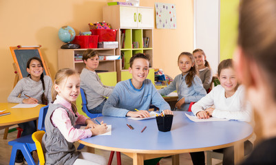 pupil with teacher sitting at table and studying