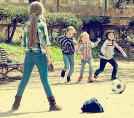 Ordinary kids playing street football outdoors