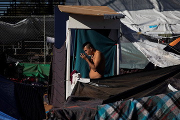 A migrant, part of a caravan of thousands from Central America trying to reach the U.S., shaves at a temporary shelter in Tijuana