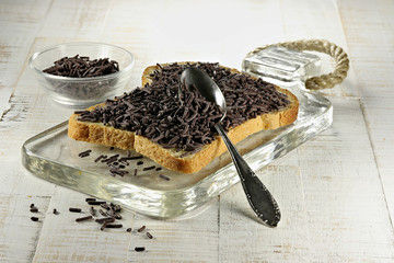 Dutch white bread with hagelslag (chocolate sprinkles) topping on glass board