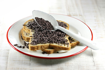 Dutch white bread with hagelslag (chocolate sprinkles) topping on enamel plate