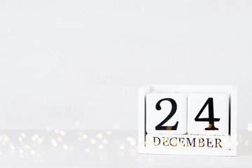 Wooden Calendar December 24 Christmas Day. On a gray background with christmas decor.