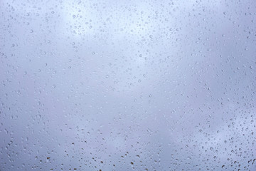 Cloudy blue sky behind window glass full of rain drop