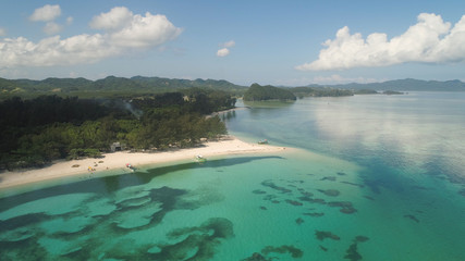 Aerial view of beautiful tropical beach with turquoise water in blue lagoon, Anguib, Philippines, Santa Ana. Ocean coastline with sandy beach, coral reefs. Tropical landscape in Asia.