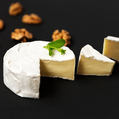 Cheese camembert or brie with walnuts on dark background. Side v