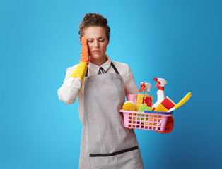 cleaning woman with basket with cleansers and brushes on blue