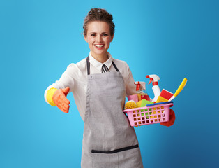 cleaning woman with a basket with cleansers and brushes giving h