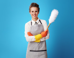 happy young cleaning woman with dust cleaning brush on blue