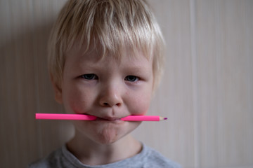 beautiful blond boy holds colored pencil in his teeth. Drawing lessons in group of preschoolers. Selective Focus, shallow depth of field