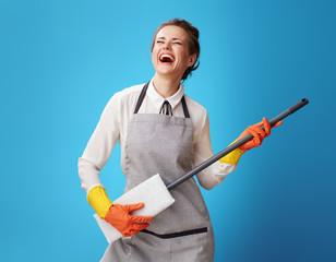 happy young cleaning woman in apron on blue using mop as guitar