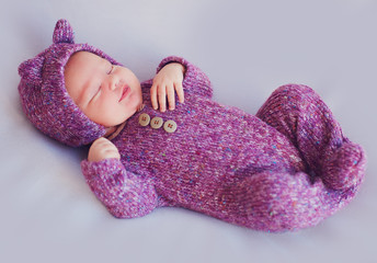 cute newborn baby girl in purple knitted overall is sleeping peacefully