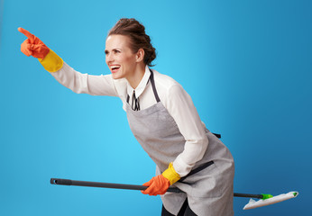 happy scrubwoman pointing at something using mop as broomstick
