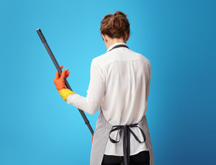 Seen from behind young housemaid in apron on blue using mop