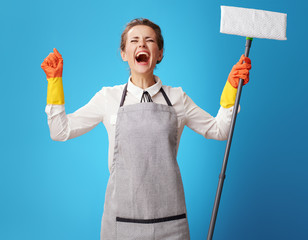 happy young cleaning woman in apron on blue with mop rejoicing