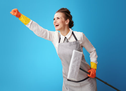 superhero style young cleaning lady in apron on blue with mop