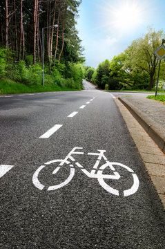 Fahrradweg Radweg Radspur auf leerer Straße mit Gegenlicht