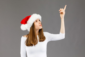 Beautiful woman in Santa Claus hat pointing on gray background