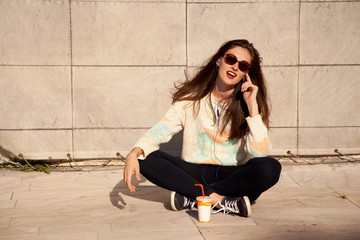 Smiling young woman sitting on street