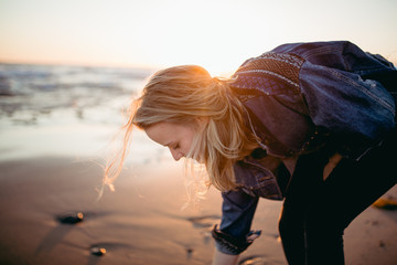 Young woman picking up shells from the sand on the beach