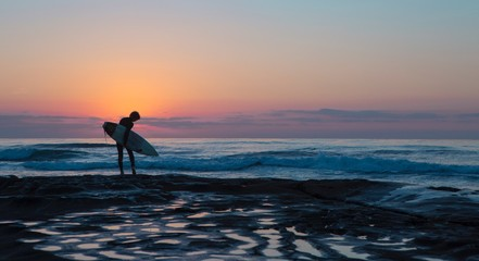 Woman holding surfboard on beach during sunset