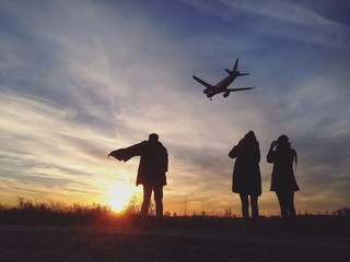 Friends looking at airplane while standing outdoors