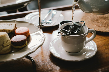 Close up of teapot pouring tea in a cup on table
