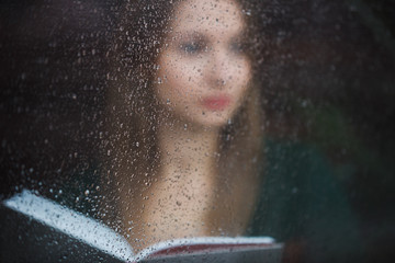Woman reading book in the cafe, view through wet window at rainy day