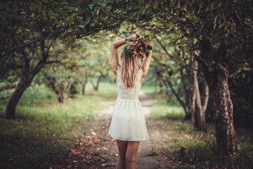 Rear view of woman holding bouquet while standing outdoors