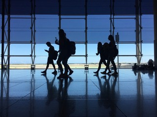 Silhouette of a passenger carrying luggage and walking at the airport
