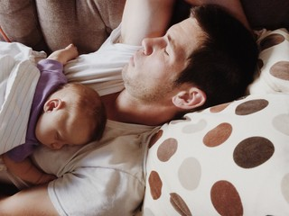 Close up of father and daughter sleeping on bed at home