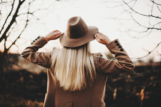 Back view of young lady in elegant jacket touching hat while standing on blurred background of autumn countryside.Elegant woman touching hat in nature